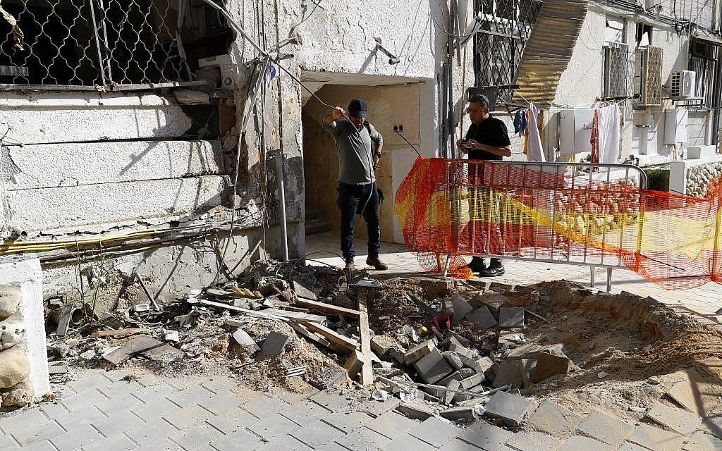 Une barrière de sécurité établie autour d'un cratère causé par une frappe à la roquette dans la ville d'Ashkelon, dans le sud d'Israël, près de la frontière avec Gaza, le 5 mai 2019 (Crédit : Jack Guez/AFP)
