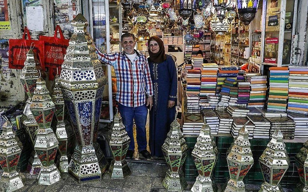 L'artisan palestinien Issam Zughair avec son épouse devant un étal de lanternes pour le Ramadan, dans la Vieille Ville de Jérusalem,, le 2 mai 2019 (Crédit : AHMAD GHARABLI / AFP)