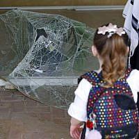 Une fillette israélienne regarde une vitre brisée à l'entrée d'un immeuble endommagé par une frappe de roquettes depuis la bande de Gaza, dans la ville d'Ashdod, dans le sud d'Israël, le 6 mai 2019. (Jack Guez/AFP)