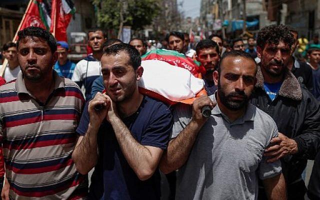 Des proches transportent le corps d'un Palestinien tué lors des frappes israéliennes la veille, durant des funérailles à Beit Lahia, dans le nord de la bande de Gaza, le 6 mai 2019 (Crédit : MAHMUD HAMS / AFP)