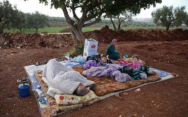 Des Syriens dans un champ près d'un camp pour les personnes déplacées dans le village d'Atmé, dans la province d'Idlib contrôlée par les djihadistes, le 8 mai 2019. (Crédit : Aaref WATAD / AFP)