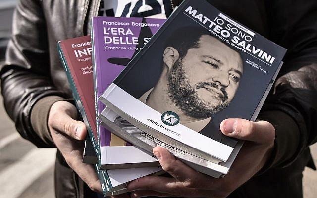 """Francesco Polacchi, patron de la maison d'édition AltaForte, tient un exemplaire de son livre """"Je suis Salvini"""" au Salon du Livre de Turin le 9 mai 2019. (Crédit : Marco BERTORELLO / AFP)"""