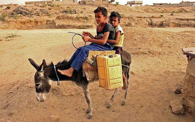 Des enfants yéménites transportent des bidons d'eau dans un camp au nord d'Abs, dans la province de Hajja, le 9 mai 2019; (Crédit : ESSA AHMED / AFP)