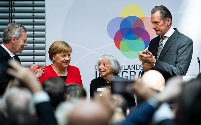 Une survivante allemande de la Shoah Margot Friedlaender félicitée par la chancelière Angela Merkel, le président de la fondation, l'ancien président allemand Christian Wulff (G) et le directeur de la maison d'édition allemande Axel Springer, Mathias Doepfner, lors d'une cérémonie célébrant le 70e anniversaire de la constitution allemande, le 14 mai 2019 à Berlin. (Crédit : Bernd von Jutrczenka/DPA/AFP)