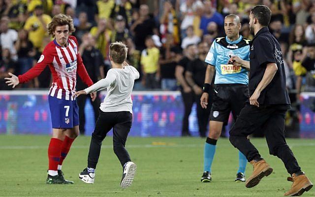 Un garçon court vers l'attaquant français Antoine Griezmann de l'Atletico Madrid lors du match de football amical opposant le Beitar Jerusalem à l'Atletico Madrid au stade Teddy de Jérusalem, le 21 mai 2019. (Crédit photo : Jack GUEZ / AFP)