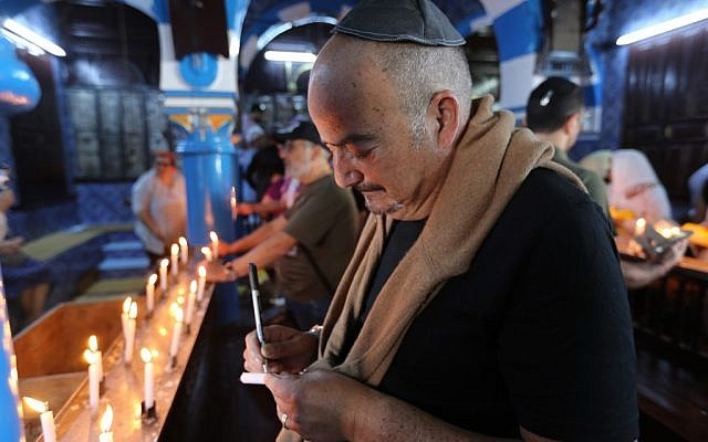 Un pèlerin juif allume une bougie le premier jour du pèlerinage annuel juif à la synagogue de la Ghriba, le plus ancien monument juif construit en Afrique, sur l'île balnéaire de Djerba, en Tunisie, le 22 mai 2019. (Crédit : FATHI NASRI / AFP)