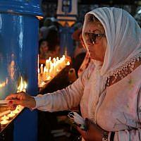 Une pèlerine juive allume une bougie le premier jour du pèlerinage annuel juif à la synagogue de la Ghriba, le plus ancien monument juif construit en Afrique, sur l'île balnéaire de Djerba, en Tunisie, le 22 mai 2019. (Crédit : FATHI NASRI / AFP)