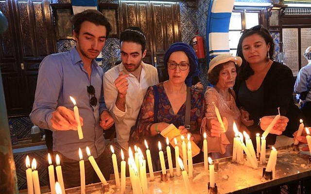 Le 22 mai 2019, des pèlerins juifs allument des bougies le premier jour du pèlerinage annuel à la synagogue El Ghriba, le plus ancien monument juif construit en Afrique sur l'île méditerranéenne de Djerba, en Tunisie. (Crédit : FATHI NASRI / AFP)