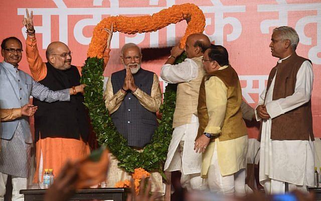 Le Premier ministre indien Narendra Modi (au centre) et le président du parti Bharatiya Janta au pouvoir, Amit Shah (2eme à droite) et le ministre de l'Intérieur indien Rajnath Singh (3eme à droite) et d'autres politiciens, fêtent la victoire de Modi aux élections nationales, à New Delhi, le 23 mai 2019. (Crédit : PRAKASH SINGH / AFP)