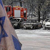 Un drapeau israélien devant des voitures très endommagées par un feu dans un contexte de chaleur extrême dans le village de Mevo Modiim dans le centre d'Israël, le 24 mai 2019 (Crédit : Jack Guez/AFP)