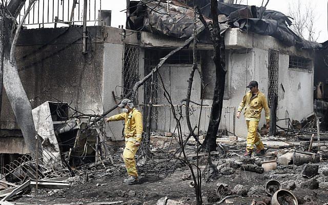 Les soldats du feu israéliens dans une habitation gravement endommagée par un incendie dans le village de Mevo Modiim, dans le centre d'Israël, le 24 mai 2019 (Crédit : JACK GUEZ / AFP)