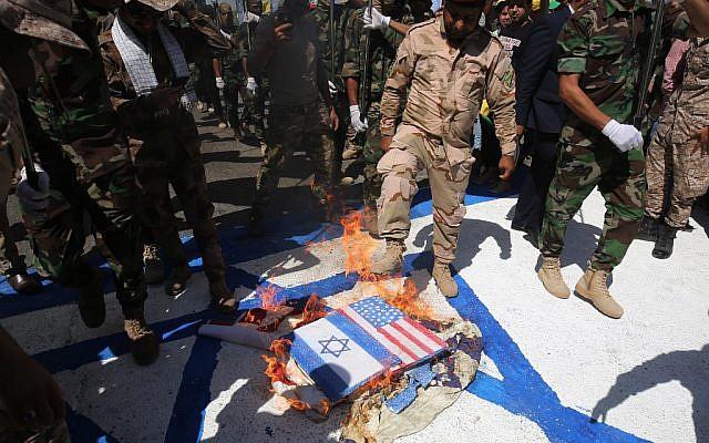 Des soldats iraniens soutenus par l'Iran et des brigades du Hezbollah brûlent des drapeaux israélien et américain pendant la journée d'Al-Qods, à Bagdad, le 31 mai 2019/. (Crédit  : AHMAD AL-RUBAYE / AFP)