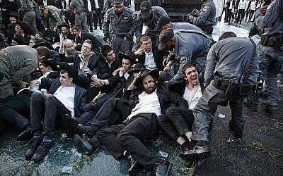 La police lance des jets d'eau pour tenter de disperser une manifestation de Juifs ultra-orthodoxes contre la conscription des membres de leur communauté dans Tsahal, à l'entrée de Jérusalem, le 23 octobre 2017. (AFP Photo/Ahmad Gharabli)