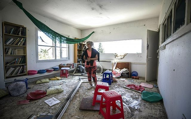 Une femme constate les dégâts causés par une roquette tirée depuis la bande de Gaza qui a touché une maison d'un moshav israélien près de la frontière avec Gaza, le samedi 4 mai 2019. (Crédit : AP / Tsafrir Abayov)