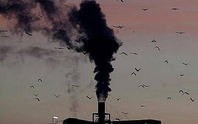 Des oiseaux devant une cheminée de fumée à Ludwigshafen, en Allemagne le 4 décembre 2018. (Crédit : AP /Michael Probst, File)