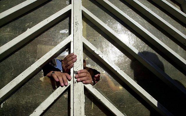 Les policiers iraniens ferment la porte du tribunal à Téhéran, le 17 juillet 2004 (Crédit : AP Photo/Vahid Salemi)