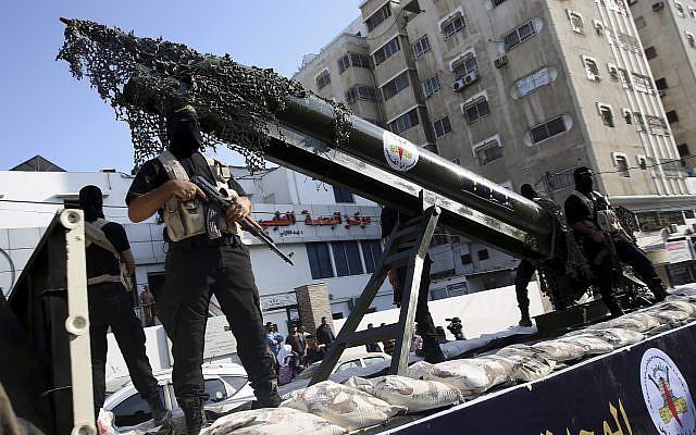 Des membres des brigades Al-Qods, la branche armée du Jihad islamique palestinien, avec un réplique d'une roquette durant une parade militaire, le 1 octobre 2018. (Crédit : AP/Adel Hana)