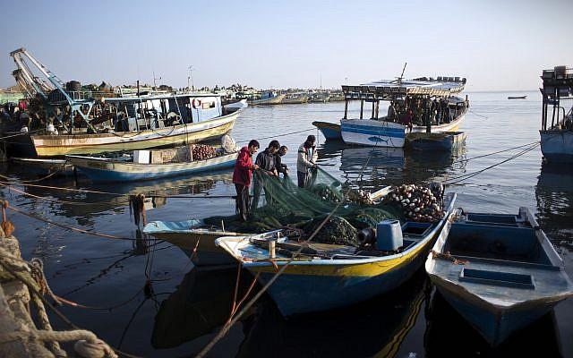 Des pêcheurs palestiniens nettoient un filet après une nuit de pêche, au port de Gaza, le 3 avril 2019. (Crédit : AP/Khalil Hamra)