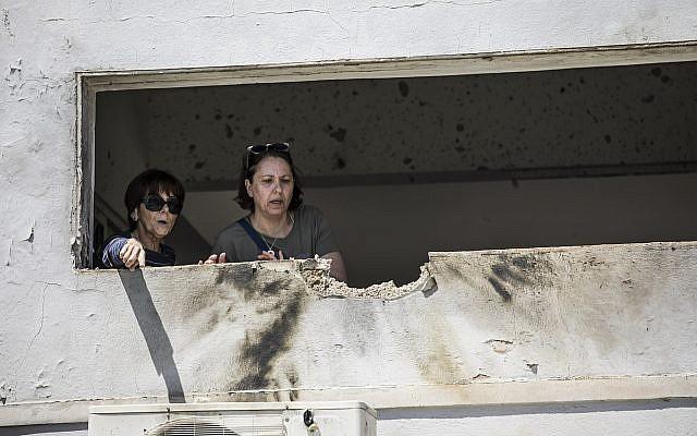 Des femmes observent les dégâts causés par une roquette tirée d'une bande de Gaza qui a touché une maison dans le sud d'Israël près de la frontière avec Gaza, samedi 4 mai 2019 (Crédit : AP / Tsafrir Abayov)