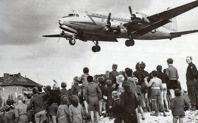 Des habitants de Berlin Ouest observent l'atterrissage d'un Rosinenbomber à Tempelhof, en 1948. (Domaine public)