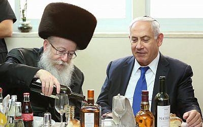 Le Premier ministre Benjamin Netanyahu est reçu par le ministre de la Santé Yaakov Litzman du parti Yahadout HaTorah (à gauche), lors d'un repas pour célébrer la naissance du petit-fils de Litzman, le 18 juin 2017. (Shlomi Cohen/FLASH90)