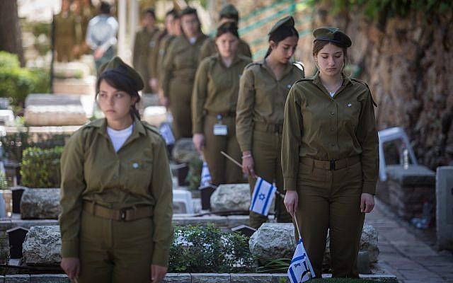 Des soldates placent des drapeaux israéliens sur les tombes de soldats au cimetière militaire du mont Herzl, à Jérusalem, le 16 avril 2018, avant Yom HaZikaron, le Jour du souvenir des soldats israéliens tombés au combat. (Hadas Parush/Flash90)