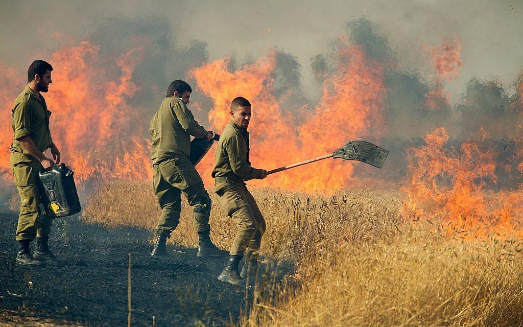 Des soldats israéliens éteignent un incendie dans un champ de Nahal Oz causé par des cerfs-volants incendiaires tirés par des Palestiniens de Gaza, près de la frontière avec la bande de Gaza, le 17 mai 2018. (Moshe Shai/Flash90