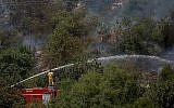 Des pompiers tentent d'éteindre un feu de forêt près de Mevaseret Zion, dans la périphérie de Jérusalem, le 22 mai 2019. (Crédit : Yonatan Sindel/Flash90)