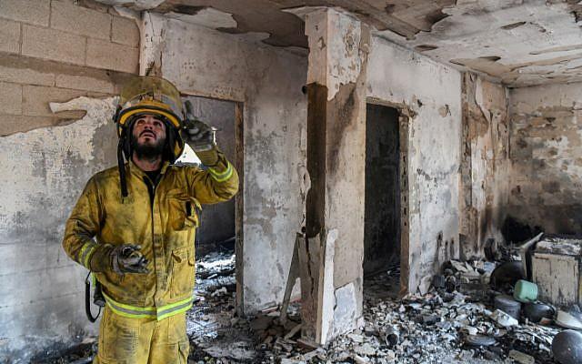 Les sapeurs-pompiers inspectent une maison ravagée par un incendie dans le kibboutz Harel, le 24 mai 2019 (Crédit : Noam Revkin Fenton/Flash90)