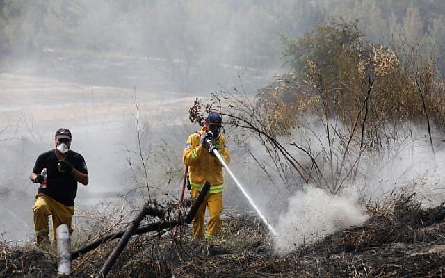 Les sapeurs-pompiers éteignent les restes d'un feu dans le kibboutz Harel, le 24 mai 2019 (Crédit : Noam Revkin Fenton/Flash90)