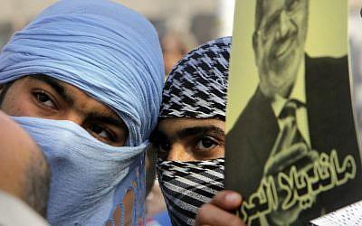 Les partisans du président destitué Mohammed Morsi couvrent leur visage durant une manifestation au Caire, en Egypte (Crédit :  AP/Amr Nabil)