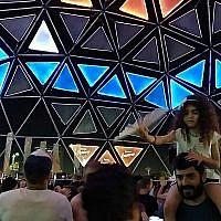 Des gens dansent dans l'un des nombreux endroits accueillant un DJ au village de l'Eurovision, au parc Charles Clore de Tel Aviv, le 16 mai 2019. (Crédit : Melanie Lidman/Times of Israel)