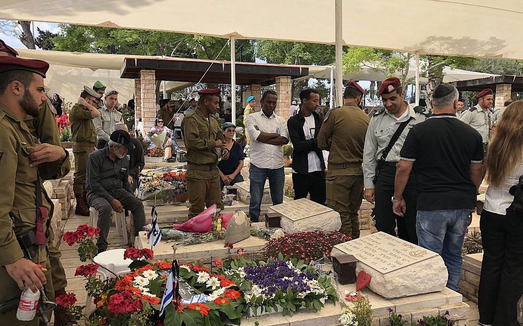 Les membres d'une famille en deuil devant la tombe de leur proche disparu au cimetière militaire d'Ashkelon à Yom HaZikaron, le 8 mai 2019 (Crédit : Jacob Magid/Times of Israel)