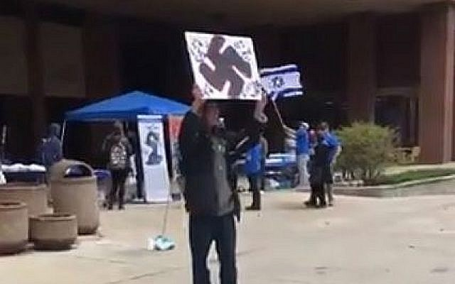 Capture d'écran d'une vidéo où l'on voit un homme muni d'un panneau avec une croix gammée lors d'une évènement pour Yom HaAtsmaout à l'université de Wisconsin-Milwaukee. (Crédit : Twitter)