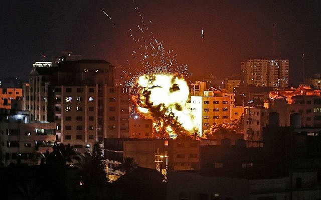 Image d'une explosion sur des immeubles lors d'une frappe israélienne à Gaza ville en riposte à des tirs de roquettes depuis l'enclave palestinienne le 4 mai 2019.  (Crédit : Mahmud Hams / AFP)