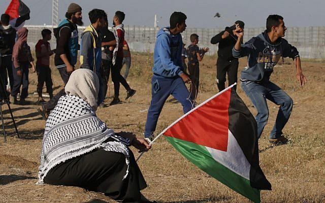 Un manifestant lance de pierres sur les soldats israéliens alors qu'une femme tient un drapeau national palestinien, lors d'une manifestation à proximité de la frontière avec Israël, à l'est de Gaza ville, le 10 mai 2019. (Said KHATIB / AFP)