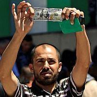 Un Palestinien montre un billet de 100 dollars reçu dans le cadre de l'aide de 480 millions de dollars allouée par le Qatar à la bande de Gaza, le 13 mai 2019.(MOHAMMED ABED / AFP)