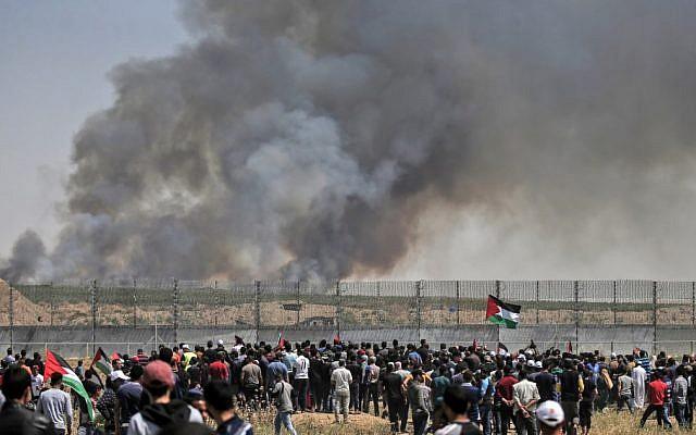 Des manifestants palestiniens participent à des émeutes le long de la barrière de sécurité à l'est de la ville de Gaza alors que de la fumée s'envole dans le ciel. L'incendie a été provoqué par un engin incendiaire attaché à un cerf volant envoyé de l'autre côté de la frontière vers Israël depuis la bande de Gaza, le 15 mai 2019. (Crédit : MAHMUD HAMS / AFP)