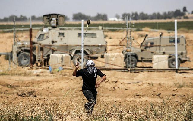 Un émeutier palestinien utilise une fronde pour lancer une pierre sur les soldats israéliens lors des manifestations de la Journée de la Nakba à l'est de Khan Younis dans le sud de la bande de Gaza, le 15 mai 2019. (Thomas COEX / AFP)