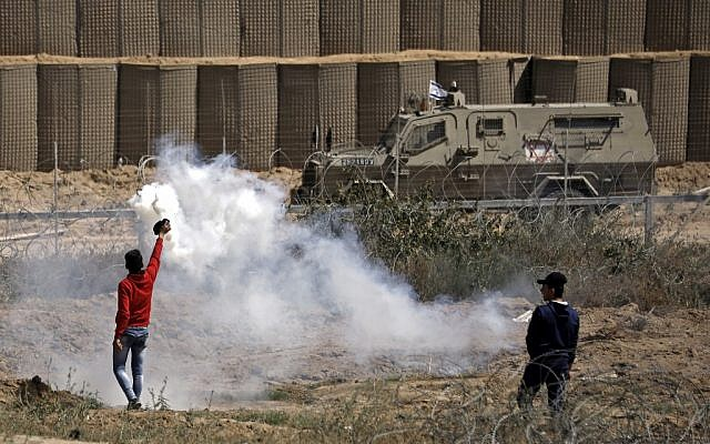 Des émeutiers palestiniens renvoient des grenades de gaz lacrymogène lors d'affrontements avec les forces israéliens lors des manifestations du Jour de la Nakba, à l'est de Bureji dans le centre de la bande de Gaza, le 15 mai 2019. (Thomas COEX / AFP)