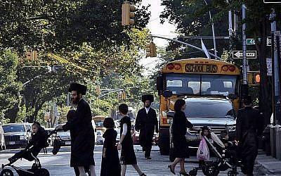 Des enfants et des adultes traversent une rue devant un bus scolaire à Borough Park, un quartier dans le quartier de Brooklyn de New York qui est le foyer de nombreux Juifs ultra-orthodoxes. (AP/Bebeto Matthews)
