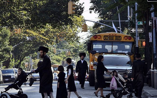 Des enfants et des adultes traversent une rue devant un bus scolaire à Borough Park, un quartier de Brooklyn, New York, qui abrite de nombreux Juifs ultra-orthodoxes. (Crédit : AP/Bebeto Matthews)