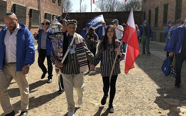 Edward Mosberg, tenant un rouleau de la Torag, lors d'une Marche des Vivants en 2018 dans l'ancien camp de la mort d'Auschwitz en Pologne. (Crédit Des profondeurs).