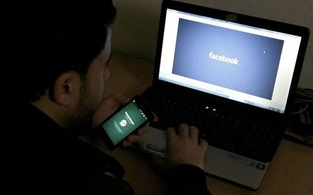Image d'un homme devant un ordinateur avec le logo Facebook, le 26 février 2014 (Abed Rahim Khatib/Flash90)