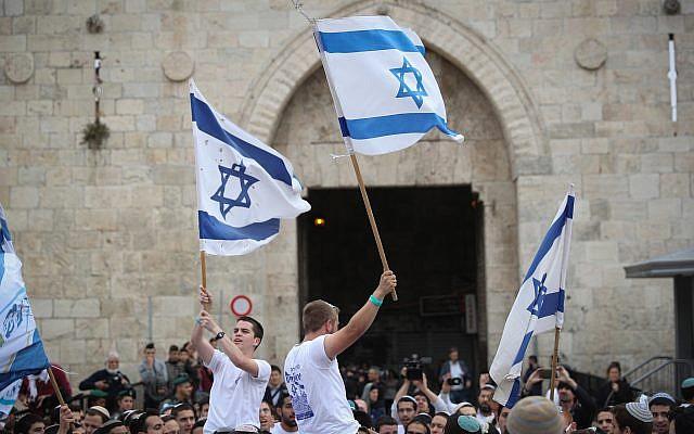 Des milliers de marcheurs juifs agitent des drapeaux israéliens alors qu'ils célèbre le Jour de Jérusalem en dansant à travers la Porte de Damas en chemin vers le mur Occidental dans la Vieille ville de Jérusalem, le 13 mai 2018. (Yonatan Sindel/Flash90)