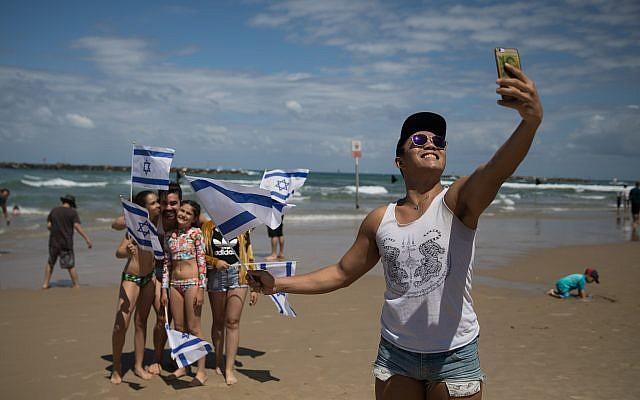 Des gens regardent la démonstration aérienne de l'armée de l'Air israélienne pour Yom HaAtsmaout sur la plage Bugrashov de Tel Aviv, le 9 mai 2019. (Crédit : Hadas Parush/Flash90)
