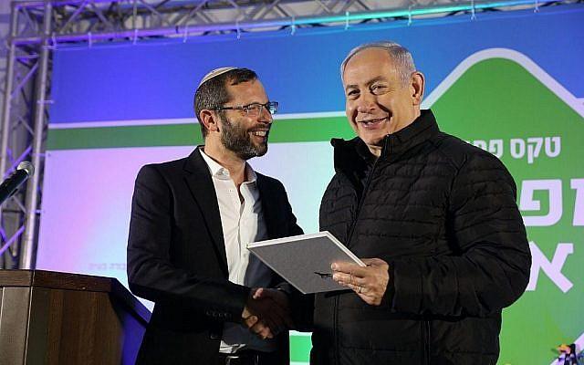 Yisrael Gantz (gauche), président du conseil régional de Binyamin, remet un prix au Premier ministre Benjamin Netanyahu à la cérémonie d'inauguration d'un nouvel échangeur à l'implantation d'Adam au centre de la Cisjordanie, le 11 décembre 2018. (Crédit: Yossi Zamir)