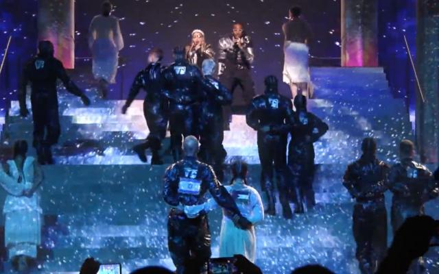 """Madonna et Quavo chantent """"Future"""" au concours de chanson de l'Eurovision alors que deux danseurs dansent bras-dessus bras-dessous avec des drapeaux israéliens et palestiniens dans leurs dos, le 18 mai 2019. (Copie d'écran : Youtube)"""