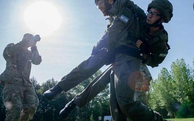 Le lieutenant Netanel Ben-Ami porte le sergent Stav Baduso lors d'une compétition américaine de photographie de guerre à Quantico, en Virginie, en mai 2019. (Crédit: armée israélienne)