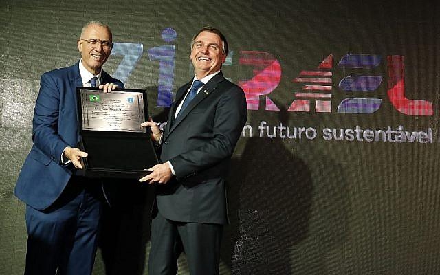 Le président brésilien Jair Bolsonaro (D) reçoit une plaque marquant le 71e anniversaire de la naissance d'Israël lors d'un événement à l'ambassade israélienne à Brasilia, le 22 mai 2019 (Crédit : autorisation de l'ambassade israélienne à Brasilia)